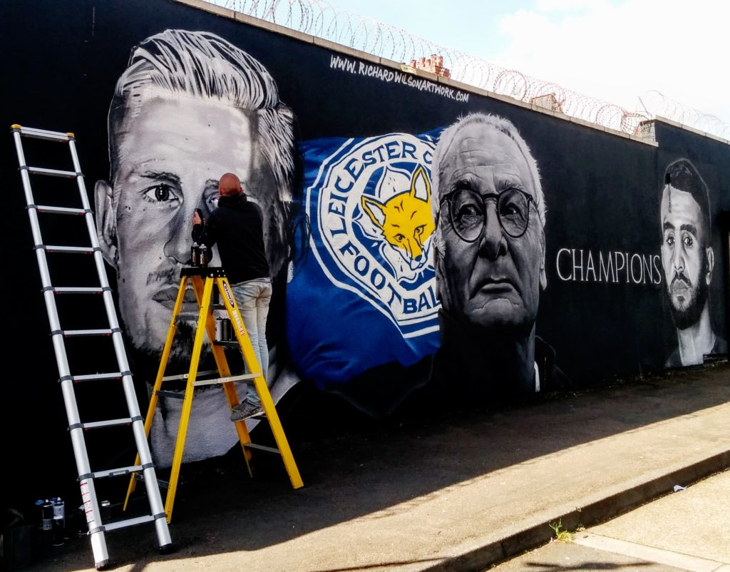 Man painting mural of football team
